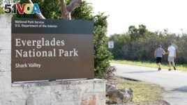 Visitors walk past a sign for Everglades National Park as they enter from overflow parking, Wednesday, Jan. 2, 2019, in Everglades National Park, Fla. Biden released a plan described in a report called