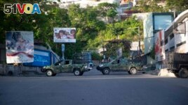 Military vehicles block the entrance to Petion Ville, the neighborhood where the late Haitian President Jovenel Moise lived in Port-au-Prince, Haiti, Wednesday, July 7, 2021. (AP Photo/Joseph Odelyn)