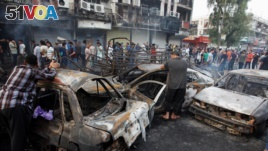 People look at cars damaged by a suicide truck attack in the Karrada shopping area of Baghdad, Iraq, July 3, 2016.
