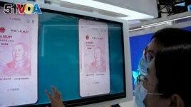 Visitors look at the e-CNY, a digital version of the Chinese Yuan, displayed during a trade fair in Beijing, China, Sunday, Sept. 5, 2021. (AP Photo/Ng Han Guan)
