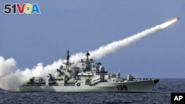 In this 2014 file photo, a Chinese warship launches a missile during a live-ammunition military drill in the South China Sea.