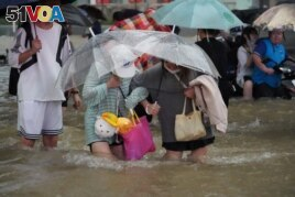 Residents, holding umbrellas amid heavy rainfall, wade through floodwaters on a road in Zhengzhou, Henan province, China July 20, 2021.