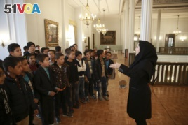 A museum guide Zeinab Sadat Asadi explains for schoolboys as they visit Niavaran Palace, now a museum, that was the primary and last residence of late shah.