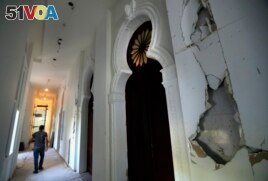 A worker walks in a corridor of the Sursock Museum that is still under reconstruction a year after being damaged in the massive explosion at the nearby port, in Beirut, Lebanon. The art collection was badly hit. (AP Photo/Hussein Malla)