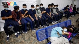 In this March 30, 2021 photo, young unaccompanied migrants wait for their turn at the secondary processing station inside a U.S. Customs and Border Protection facility in Texas. (AP Photo/Dario Lopez-Mills, Pool, File)