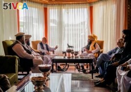 In this handout photograph released by the Taliban, former Afghan President Hamid Karzai, center left, senior Haqqani group leader Anas Haqqani, center right, Abdullah Abdullah, second right, head of Afghanistan's National Reconciliation Council.