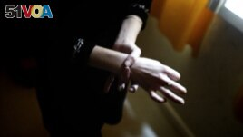 FILE - Helene, a 28-year-old woman, shows the size of her wrist as she stands in her apartment in Bourges, France. She had been diagnosed with anorexia. (AFP Photo)