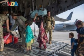 In this image provided by the U.S. Air Force, U.S. Air Force loadmasters and pilots assigned to the 816th Expeditionary Airlift Squadron, load people being evacuated from Afghanistan onto a U.S. Air Force C-17 Globemaster III at Kabul's airpoty.