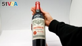 A woman holds a bottle of Petrus 2000, a space-aged bottle of fine French wine part of a case of Bordeaux that was literally matured in Earth orbit for 14 months. (REUTERS/Gonzalo Fuentes)