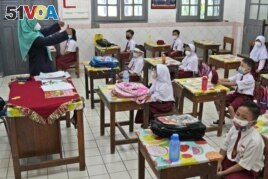 Students wearing face masks to help prevent the spread of COVID-19 attend a class during the first day of school reopening at an elementary school in Jakarta, Indonesia, Monday, Aug. 30, 2021(AP Photo/Dita Alangkara)