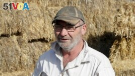 Bruce Barnes talks in front of stored hay infested with mice on his family's farm near Bogan Gate, Australia on May 20, 2021. (AP Photo/Rick Rycroft)