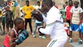 Boxer Tijani Abdulazeez, popularly known as TJ, 15, trains with his father, Abdulfathi Abdulazeez, at an outdoor boxing gym in Adura playground, in Lagos, Nigeria. REUTERS/Temilade Adelaja