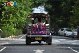 Tuk-tuk driver Samran Thammasa rides his vehicle decorated with a banner of K-pop star Jessica Jung, in Bangkok, Thailand May 12, 2021. (REUTERS/Chalinee Thirasupa)