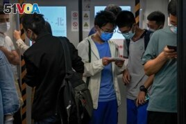 Students play online games inside a subway train in Beijing Tuesday, Sept. 14, 2021. China has set new rules limiting the amount of time kids can spend playing online games. (AP Photo/Andy Wong)