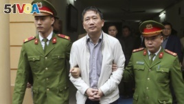 FILE - Trinh Xuan Thanh, center, is led out of a courtroom by police officers in Hanoi, Vietnam, Monday, Jan. 22, 2018. Germany accused Vietnam of kidnapping Thanh from a Berlin park in July, the charge Vietnam denied saying Thanh turned himself in to police voluntarily. (An Dang/Vietnam News Agency via AP)