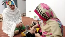 Rani Khan, a transgender woman who teaches the Quran at Pakistan's first transgender only madrasa or a religious school, looks at one of her students during a tailoring lesson in Islamabad, Pakistan March 10, 2021. (REUTERS/Salahuddin)