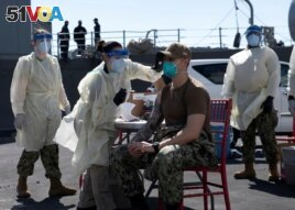 FILE - A United States Navy officer from the USS San Diego receives a vaccine against coronavirus at the navy port in Manama, Bahrain in this picture taken February 26, 2021 and released by U.S Navy on February 27, 2021. (Brandon Woods/U.S. Navy/Handout via REUTERS)