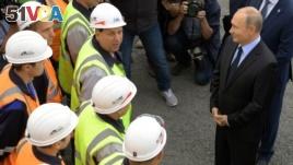 Russian President Vladimir Putin, right, speaks to workers as he visits Chernigovets coal mine in Beryozovsky, Kemerovo region, Russia, Monday, Aug. 27, 2018. (Alexei Druzhinin, Sputnik, Kremlin Pool Photo via AP)