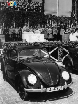 Nazi leader Adolf Hitler speaks prior to laying the cornerstone for a giant automobile factory in Fallersleben near Hanover, Germany, May 26, 1938. In the foreground is a Beetle car. (AP Photo)