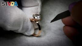 A worker inspects a ring set with an Aether diamond made from captured CO2, at the RFG Manufacturing Riviera jewelry design facility in New York City, New York, September 30, 2021. (REUTERS Mike Segar)