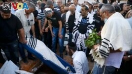 In this May 18, 2021 file photo, mourners attend the funeral of Yigal Yehoshua, 56, at a cemetery in Hadid, central Israel. (AP Photo/Oded Balilty, File)