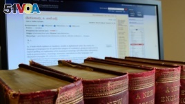 This undated image released by the Oxford English Dictionary (OED) shows old volumes of the dictionary next to a computer monitor displaying a page from the OED website. The OED has added about 1,000 new entries.