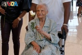 Viola Fletcher, center, the oldest living survivor of the Tulsa race massacre, holds a rose she received as she arrives for a luncheon honoring survivors Saturday, May 29, 2021, in Tulsa, Okla. (AP Photo/Sue Ogrocki)