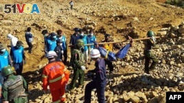 Soldiers carry the bodies of miners killed by a landslide in a jade mining area in Hpakhant, in Myanmar's Kachin state on November 22, 2015.