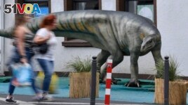 FILE - Pedestrians pass a life-size replica of a Plateosaurus dinosaur in the city center of Bochum, Germany, Monday, Aug. 12, 2019. (AP Photo/Martin Meissner)