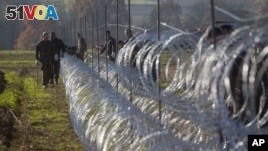 Slovenian soldiers erect a razor-wired fence on the Croatian border in Gibina, Slovenia, Nov. 11, 2015. The government aims to prevent the uncontrolled entry of more migrants in the already-overwhelmed alpine state.  (AP Photo/Darko Bandic)