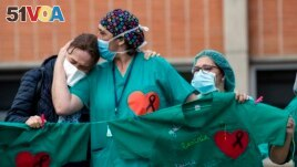 Health workers comfort each other during a memorial for a co-worker who died of COVID-19, at the Severo Ochoa Hospital, in Leganes, Spain, April 10, 2020.