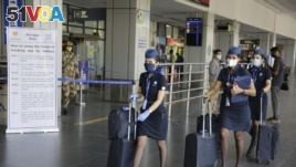 Crew members of an airline arrive at the airport as domestic flights resume operations after nearly two-month lockdown amid the COVID-19 pandemic in Ahmedabad, India, Monday, May 25, 2020. (AP Photo/Ajit Solanki)
