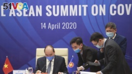 Vietnamese Prime Minister Nguyen Xuan Phuc, left, and his staff prepare documents ahead of the Special ASEAN summit on COVID-19 in Hanoi, Vietnam Tuesday, April 14, 2020. ASEAN leaders met with their counterparts from China, Japan and South Korea.