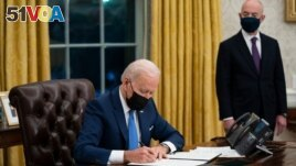 FILE - Secretary of Homeland Security Alejandro Mayorkas looks on as President Joe Biden signs an executive order on immigration, in the Oval Office of the White House, Feb. 2, 2021, in Washington.