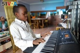 A boy plays strikes a chord on his keyboard inside his apartment during the spread of the coronavirus disease (COVID-19), in Kinshasa, Democratic Republic of Congo April 18, 2020. (REUTERS PHOTO/Kenny Katombe)
