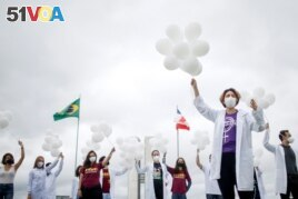 Nurses hold balloons during a protest asking for COVID-19 vaccines, in Brasilia, Brazil, April 7, 2021.