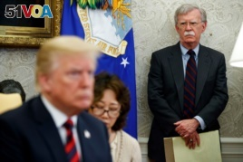 FILE - U.S. President Donald Trump, left, conducts a meeting in the Oval Office of the White House in Washington, May 22, 2018, as then-National Security Adviser John Bolton, right, looks on.