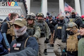 FILE - Jessica Watkins, second from left, and Donovan Crowl, center, both from Ohio, march down the east front steps of the U.S. Capitol with the Oath Keepers militia group among supporters of President Donald Trump in Washington, Jan. 6, 2021.