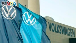 Flags wave in front of a factory building during the production restart of the plant of the German manufacturer Volkswagen AG (VW) in Zwickau, Germany, Thursday, April 23, 2020.