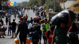 FILE - Migrants carry their belongings as they flee a road leading from Moria to the capital of Mytilene, on the northeastern island of Lesbos, Greece, Sept. 17, 2020.