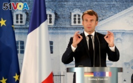 French President Emmanuel Macron gestures as he gives a press conference, at the German government's guest house Meseberg Castle in Gransee near Berlin, Germany, Monday, June 29 2020.